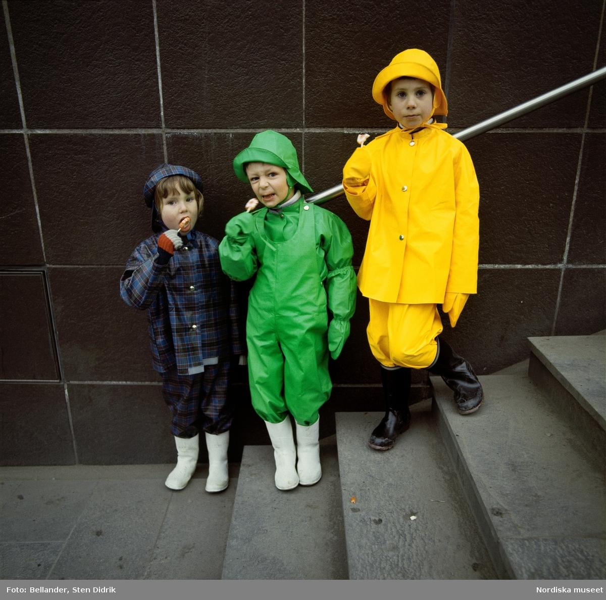 Tre barn i färgglada regnkläder står i en trappa med varsin godisklubba.