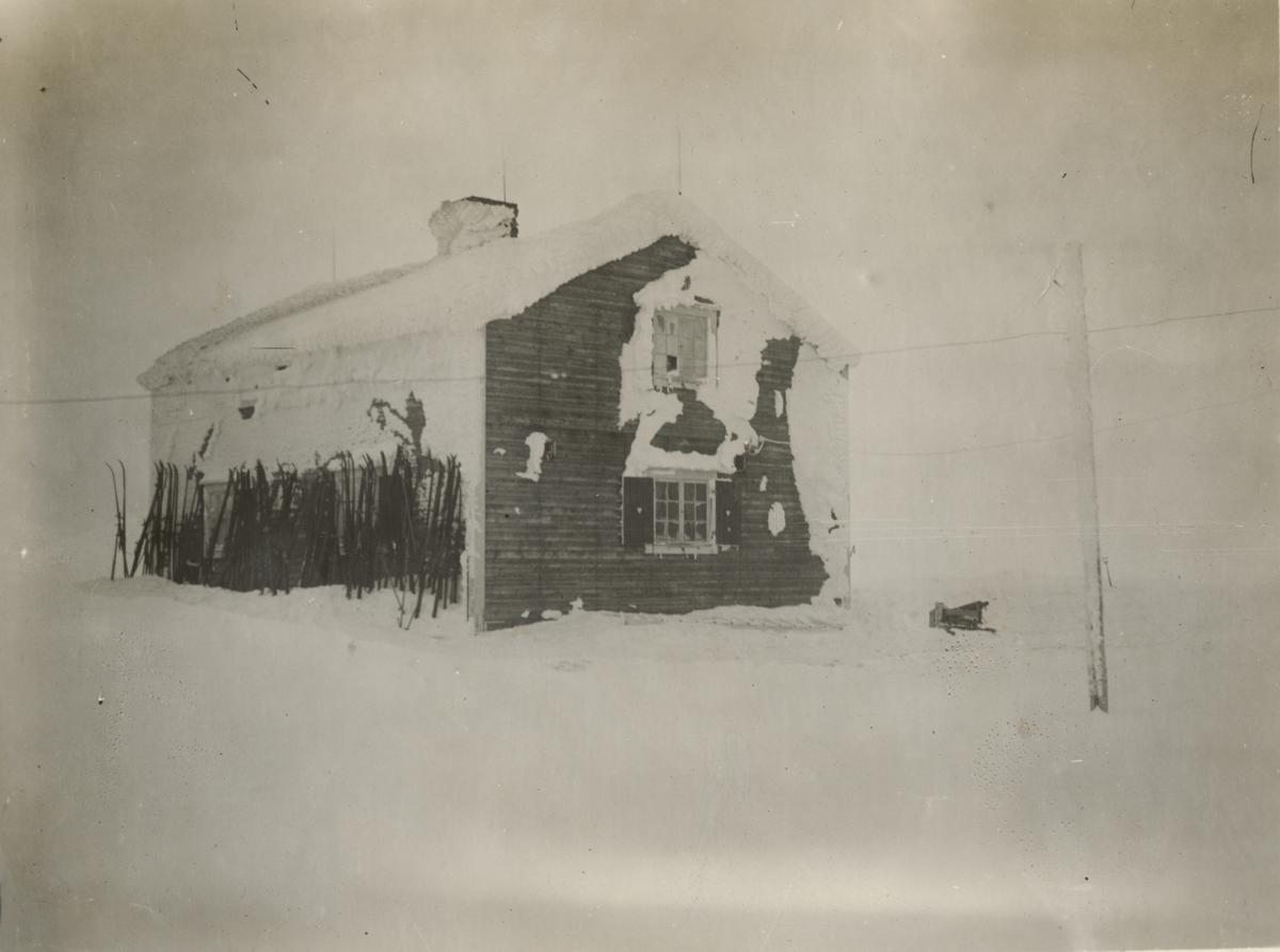 Ett trähus på fjällen. Husväggarna är delvis täcka av snö. Mot ena husväggen står skidor lutade.