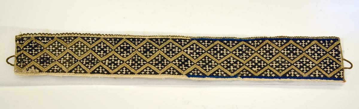 Fra protokollen:  Kvarde i bomuldstöi sydd i korssøm med grønne løkker i øvre kant. Mønster: zikzakborder i gult begrændser rhomber i sort, hvor 4 korsstillede motkors danner det iøiefallende ornament.