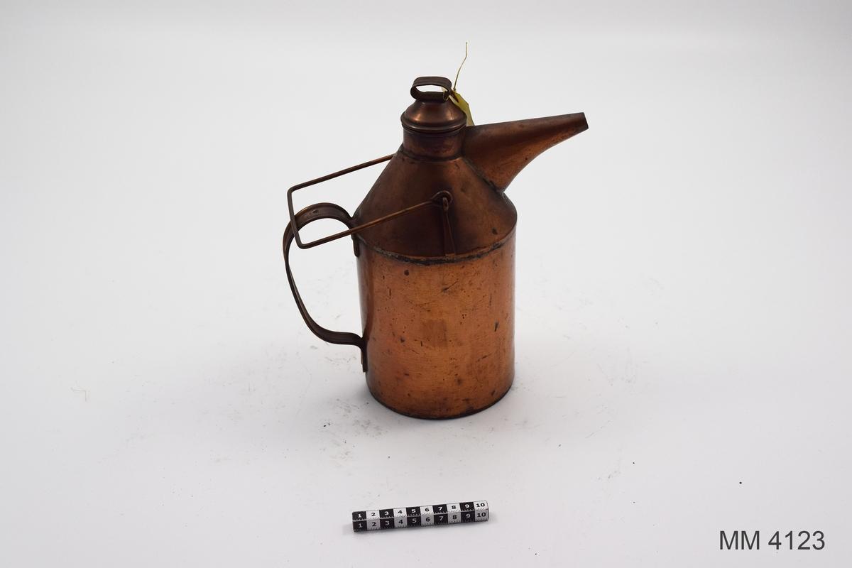 Oljeflaska. Den är cylindrisk med konisk överdel och cylindrisk hals med losk. På den koniska delen pip för tömning och rörligt bärhandtag. På motsatta sidan på cylindriska delen fast handtag. Märkt med kronstämpel på fasta handtaget.