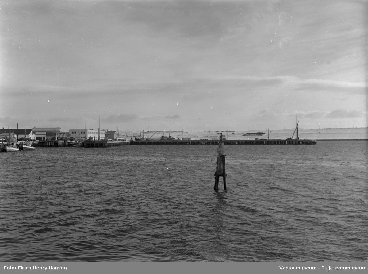 Vadsø april 1952. Bildet er tatt fra fastlandet mot syd. Vi ser havna med Dampskipskaia og dampskipsekspedisjonen midt i bildet. Videre ser vi flere kaianlegg, fiskebåter, tanker, bygninger. I bakre billedkant ser vi Vadsøya og noen bygninger.
