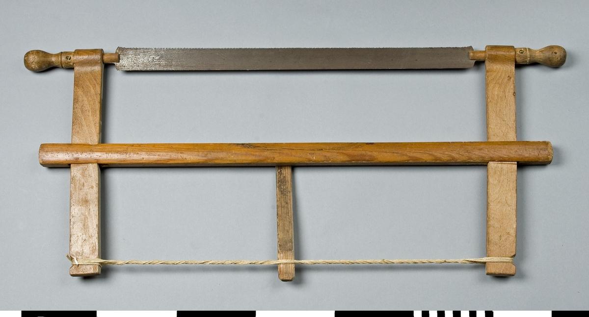 Såg med ställning av trä. Ställningen består av en bom av furu och två sågarmar av bok. Sågbladet av stål är inspänt i ställningen mellan sågarmarna med hjälp av en spännpinne av furu och ett snöre. Genom den ena änden av varje sågarm går en svarvad knopp som är vridbar. Bladet är fäst i denna och kan ställas snett. Sågbladet är fintandat. Sågen användes vid sinkning och annan finsågning.  Funktion: Rörlig sågklinga för vågrät och lodrät sågning av skivor