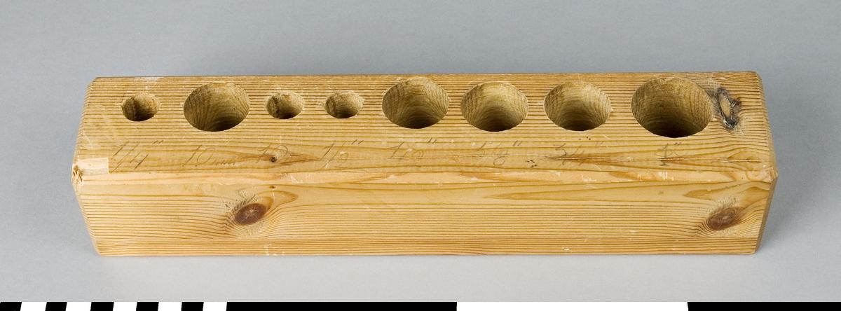 Ställ av trä för uppställning av stämborrar. Borrstället har 8 hål med olika diametrar.  Funktion: Förvaring av stämborrar