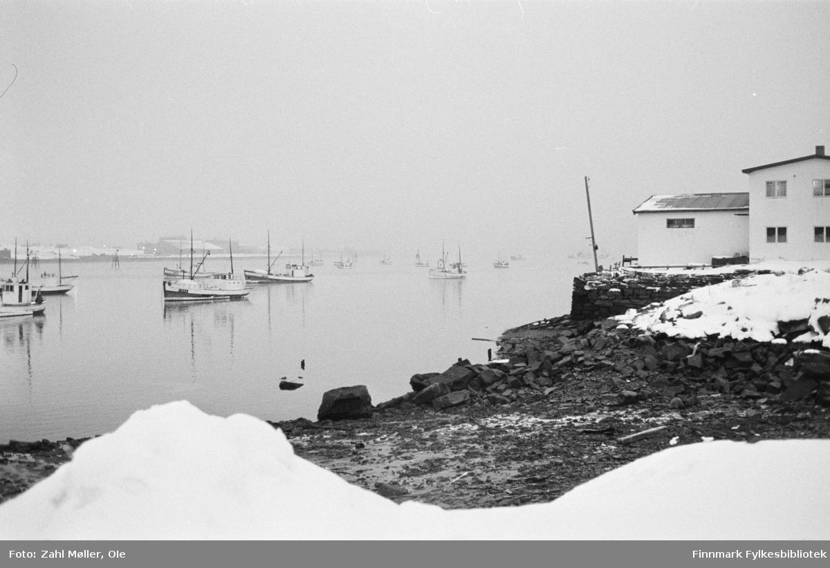 Bildeserie tatt i Vadsø i perioden 1968-69 av Vadsøfotografen Ole Zahl Mölö. Dette vinterbildet er tatt i 1968. Bildet viser fiskeskøyter som ligger fortøyd i Vadsø. En stor snøhaug i front vitner om store snømengder. I bakgrunnen skimtes Vadsø Sildoljefabrikk som var i drift fra 1953-2009.