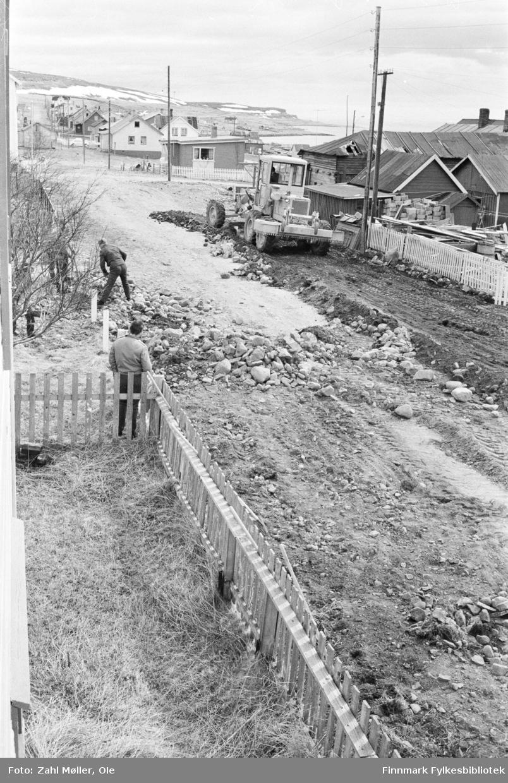 Vadsø 1969. Fotoserie av Ole Zahl Mölö. Veiarbeid og dosering av jord og stein. En mann i arbeid og en som står og bivåner arbeidet.