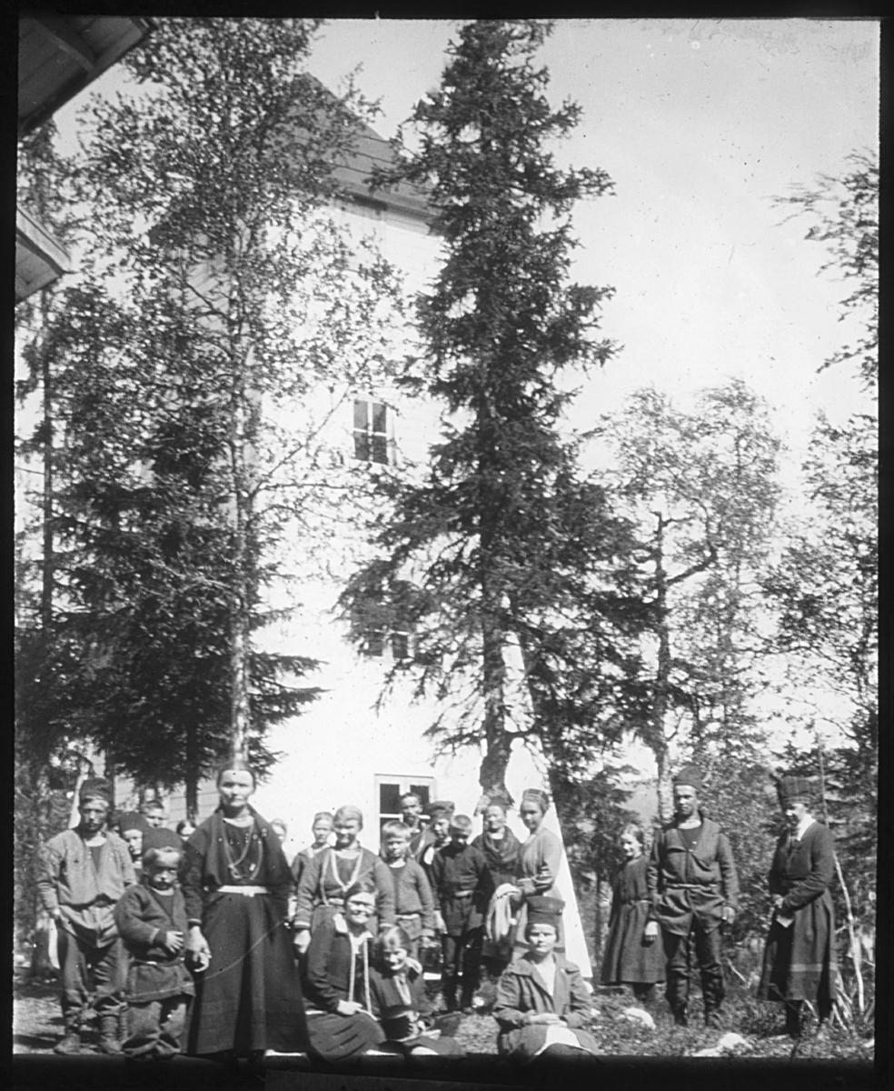 """""""(N.950.) Majavannstårnet. Dg. 40."""" står det på glassplaten. Gruppebilde av samiske kvinner og menn foran Majavannstårnet. Det er sol og løv på bjørketrærne. Øverst i høyre hjørne kan man se deler av et møne fra et annet bygg i nærheten. Kvinnene og mennene har samiske drakter og hatter eller luer. Bildet viser Majavatn Misjonshus og tårnet på Majavatn kirke. En automobil står parkert øverst i bakken. Bildet er del av en serie bildedokumentasjon gjort for Finnemisjonen av fotograf Alf Schrøder i Trondheim. Majavatn Misjonshus ble brukt til samlinger for sørsamene. Majavatn (sørsamisk: Maajehjaevrie) er ei grend i Grane kommune i Nordland. Stedet ligger ved Store Majavatn, like ved grensen til Nord-Trøndelag. Det drives sørsamisk reindrift i områdene rundt Majavatn. Majavatn kirke og Stevneplassen ved Majavatn ble etablert av Finnemisjonen i 1915 som møtested for samer. Finnemisjonen ble senere omdøpt til Norsk Samemisjon. Stevneplassen ved Majavatn ble fast etablert gjennom innvielsen av Majavatn misjonshus 18.juli 1915. Misjonshuset ble bygget som ledd i Finnemisjonens virksomhet blant sørsamer, og initiativtakeren var emissær Paul Pedersen fra Trondheim. Området har vært samlingssted for sørsamer gjennom lang tid; dette kan dokumenteres tilbake til ca 1730. De første samlingene var på Hesjevollen ved Tomasvatnet, og sammenkomstene hadde et variert preg: dels kristelige samlinger, dels et sted hvor lappefogdene utførte embetshandlinger og dels et markedsstevne med fester, servering og sosial omgang. Forhåndsdrøftinger omkring etableringen av Norske Reindriftsamers Landsforbund foregikk her. Stevneplassen brukes fortsatt i samisk kristen sammenheng. Samlingsplassen kan også sees av tradisjonell samisk sijteorganisering."""