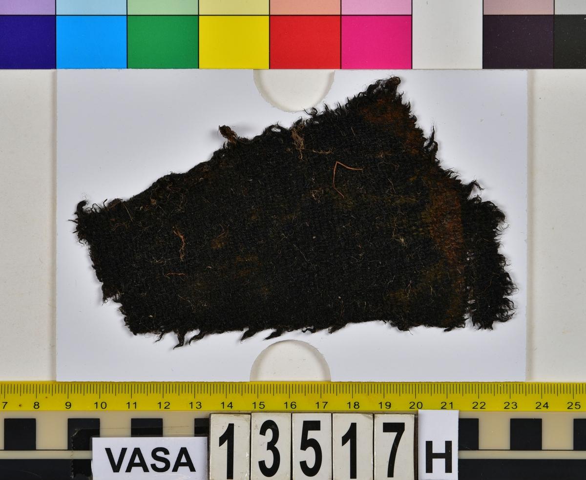 Textil. 20 textilfragment uppdelade på fyndnummer 13517a-j. Fnr 13517a består av två fragment av ull vävda i tuskaft. Det mindre fragmentet är trekantigt, har varit valkat på insidan och har fållar med sömmar kvar. Det stora fragmentet har två bevarade originalkanter. Fnr 13517b består av två fragment av ull vävda i 2/1-kypert. Fnr 13517c består av två fragment av ull vävda i tuskaft. Det större fragmentet har ett hål i mitten. De är svarta av tjära och har troligen varit en del av en becksudd. Fnr 13517d består av ett fragment av ull vävt i 2/1-kypert. Fnr 13517e består av ett fragment av ull vävt i 2/2-kypert. Fnr 13517f består av ett fragment av ull vävt i tuskaft. Fnr 13517g består av 6 fragment av ull vävda i tuskaft. Två av fragmenten ser ut att ha varit valkade på ena sidan. Tre av fragmenten har vissa originalkanter eller -fållar kvar. Fnr 13517h består av ett fragment av ull vävt i tuskaft. Fnr 13517i består av 3 fragment av ull vävda i tuskaft. Fragmenten kan ha varit valkade på ena sidan. Ett fragment är ljusare i färgen än de andra. Fnr 13517j består av ett filtat fragment av ull eller bäver. I en av kanterna finns hål efter en söm.