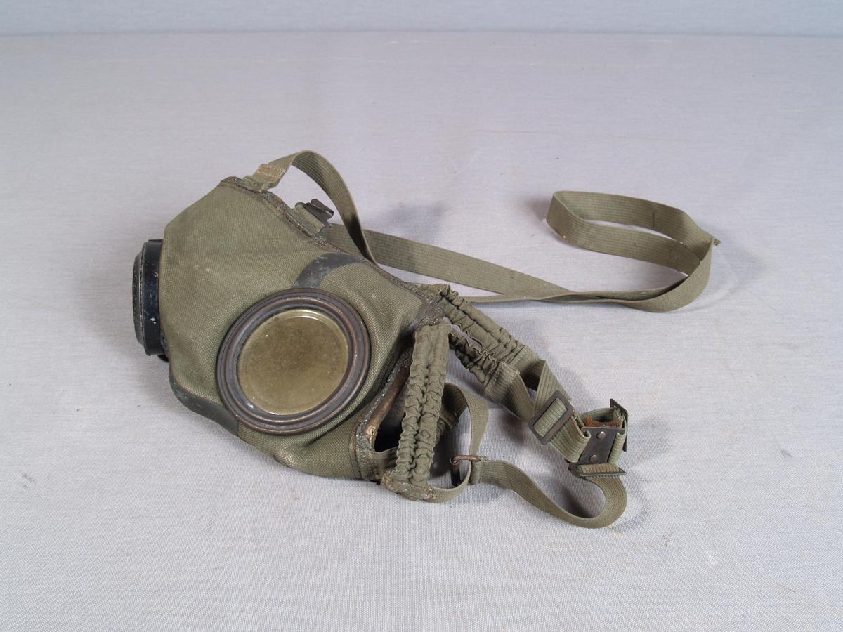 Gassmaske i bomullslerret, kantet med lær  på innsiden. Sirkelrunde øyeglass, sirkelrundt gjenget hull for tilkobling til filter. Festeremmer i tekstil.