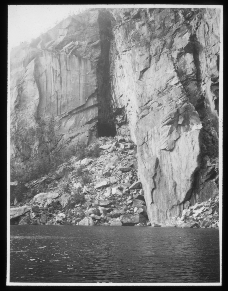 «N.575b)  Hule ved Hellesmobotn, Lofoten. N.9. Foto: Schrøder, T.hjem» står det på glassplaten. Hellmobotn (lulesamisk: Vuodnabahta) ligg i Tysfjord kommune. Med 6,3 km i luftline mellom havet og grensa til Sverige er det her Noreg er på sitt smalaste sør for Finnmark. Rundt Hellmofjorden er det høge fjell på alle kantar. Hellmofjorden er ei fortsetjing av Tysfjorden, som igjen er ein sidefjord til Vestfjorden. Ein del av Atlanterhavet når med det her heilt inn til den skandinaviske høgfjellkjeda Kjølen. Under 2. verdskrig var dette ei mykje nytta rute for flyktningar for å kome seg over til Sverige på grunn av den korte distansen. Dette vart tyskarane fort klar over, og framleis kan ein sjå fleire bunkrar langs stien opp mot svenskegrensa.(Kilde: Wikipedia).