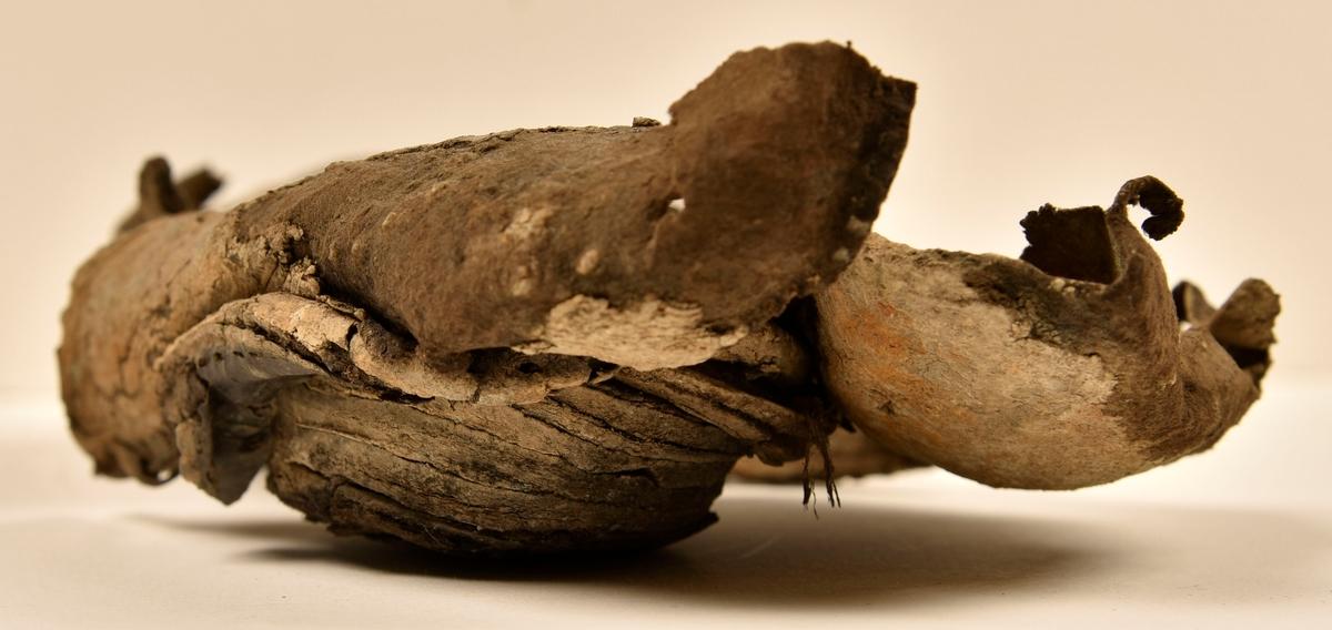 En delvist fragmentarisk sko. Troligtvis rör det sig om en slejfförsedd hålsko. Ovanlädret sitter fästat vid skon och är delvist fragmentariskt. Vid hälpartiet sitter två stycken sidostycken. Sidostyckena sluter om hälpartiet. Styckena har suttit fästade vid varandra mitt bak på skon. Bottnen består av tre sulor och klacklappar. Yttersulan är avskuren vid partiet för hålfoten. Mellan två av sulorna sitter fem klacklappar fästade med träpligg. På skons undersida, vid tå- och hälpartiet, finns kvarsittande träpligg. Ovanlädret, sulor och bakkappor har kvarsittande tråd. Även ca 12 stycken små läderfragment. Lädret är sprött och hårt och har blå- och rostliknande utfällningar. Lädret tycks vara obehandlat. Ytterligare två läderfragment har fått fyndnummer 23070f.  Textil. Fnr 23070a är ett stickat tygfragment av ull som sitter fast på läder. Under lädersulan finns mycket orangeröd korrosion. I fyndnumret ingår även tre små läderfragment samt två små stickade fragment. Det ena av de små läderfragmenten har en söm på mitten. Fnr 23070b är 40 slätstickade tygfragment av ull varav ett sitter fast på läder och korrosion. Fnr 23070c är 17 fragment av ull vävda i 2/2-kypert. På åtminstone fem av fragmenten har det fastnat ett slätstickad tygfragment, som de i fnr 23070a-b, på ena sidan av det vävda tyget. Fnr 23070d innehåller 32 fragment av läder och korrosion, 1 träpligg samt 4 textilfragment. Av textilfragmenten är 3 stickade och 1 är vävd. Fnr 23070e består av 21 fragment av ull vävda i tuskaft samt 17 snörliknande fragment som eventuellt är tillverkade av växtfibrer. Snörets bredd är 3-4 mm.