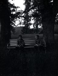 Två pojkar på en bänk på Tuna gård.