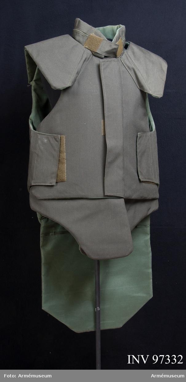 Kroppsskyddsväst i grågrön textil med insydda plattor. Västen spännes med kardborreband. Det finns etikett med tillverkarnamn och tvättinstruktion på finska i västen.