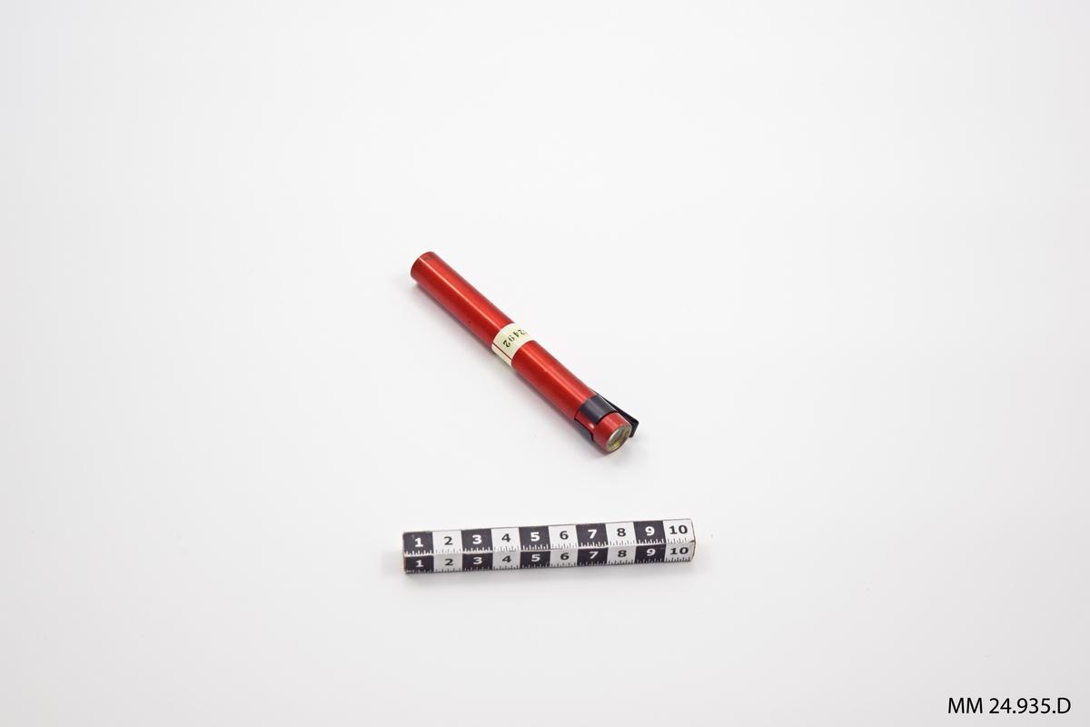 """Rött metallrör. I ena änden sitter en stickkontakt med en pol. I andra änden finns ett litet okular som man kan titta in i. Längst upp en svart hållare för att fästa dosimetern i en ficka eller dylikt. Text i relief på hållaren: """"BENDIX"""". Mitt på dosimetern sitter en vit lapp med svart text: """"21-600- 022492"""""""
