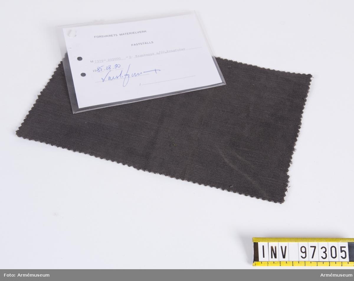 """Vidhängande modellapp med text: """"Försvarets materielverk. Fastställs. M 7379-203000-2. Regnkappa m/60, Kragfoder 1985-08-20. (oläslig sign)"""""""