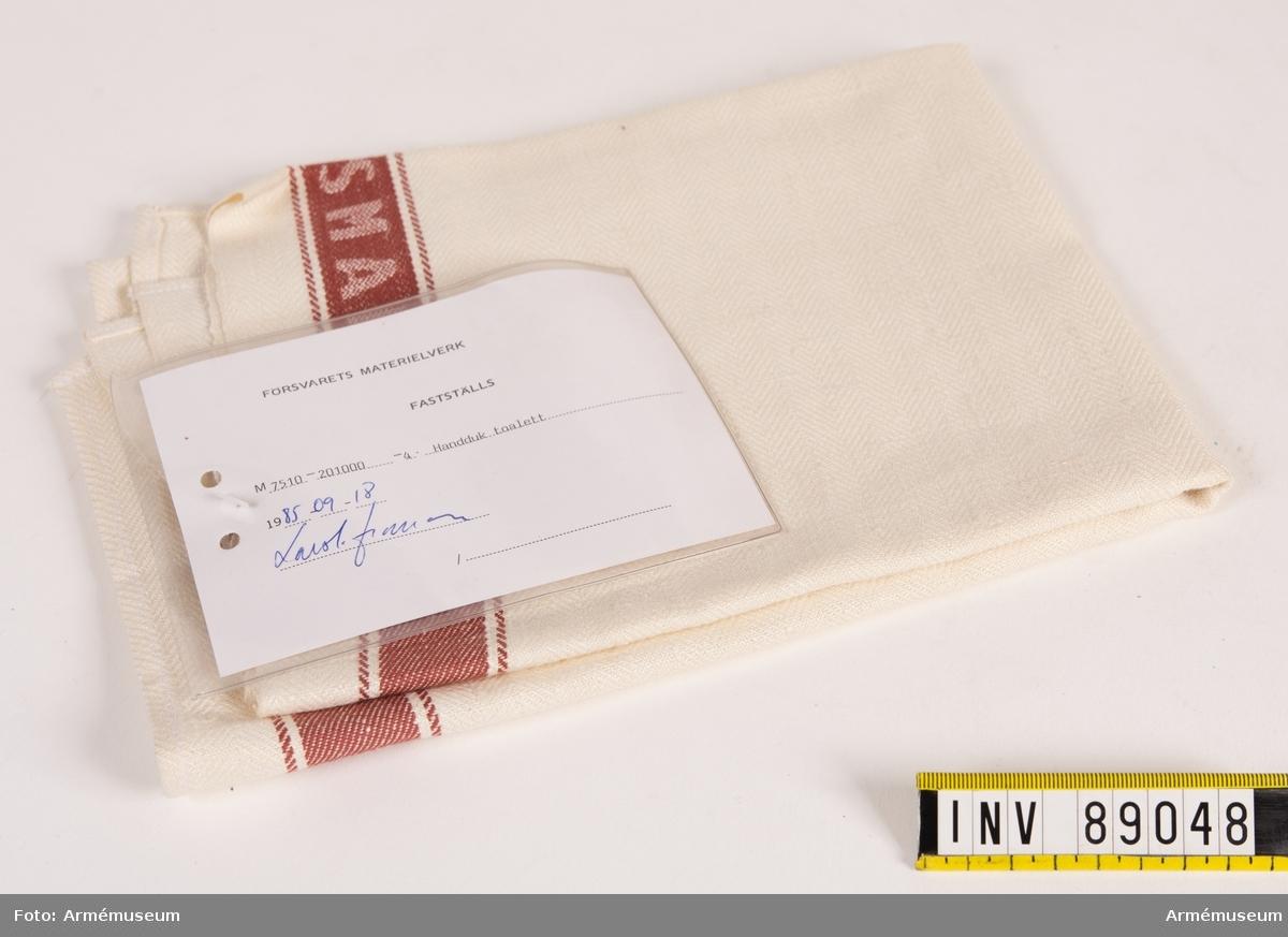 """Handduk i vävd linne med röd-brun bård runt om. På båda långsidorna i den röda bården är ordet FÖRSVARSMAKTEN invävt. På baksidan hällor i rött bomullsband för upphängning på respektive kortsida. Vidhängande modellapp med text: """"Försvarets materielverk. Fastställs. M 7510-201000-4 Handduk toalett 1985-09-18. (oläslig underskrift)."""""""