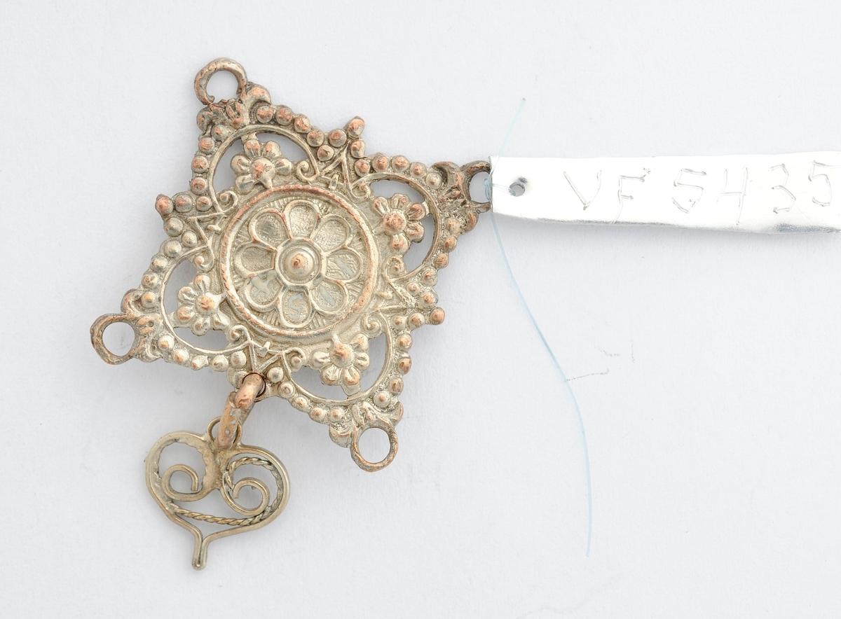 Del av sølje (?), Form som ei firkanta plate med delvis gjennombrote mønster. Ein ring med eitt hjarteforme heng.