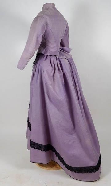 Enligt liggaren: Klänning lila, halvsiden, mycket litet begagnad, enkelt sydd, kjolen med svarta spetsar.