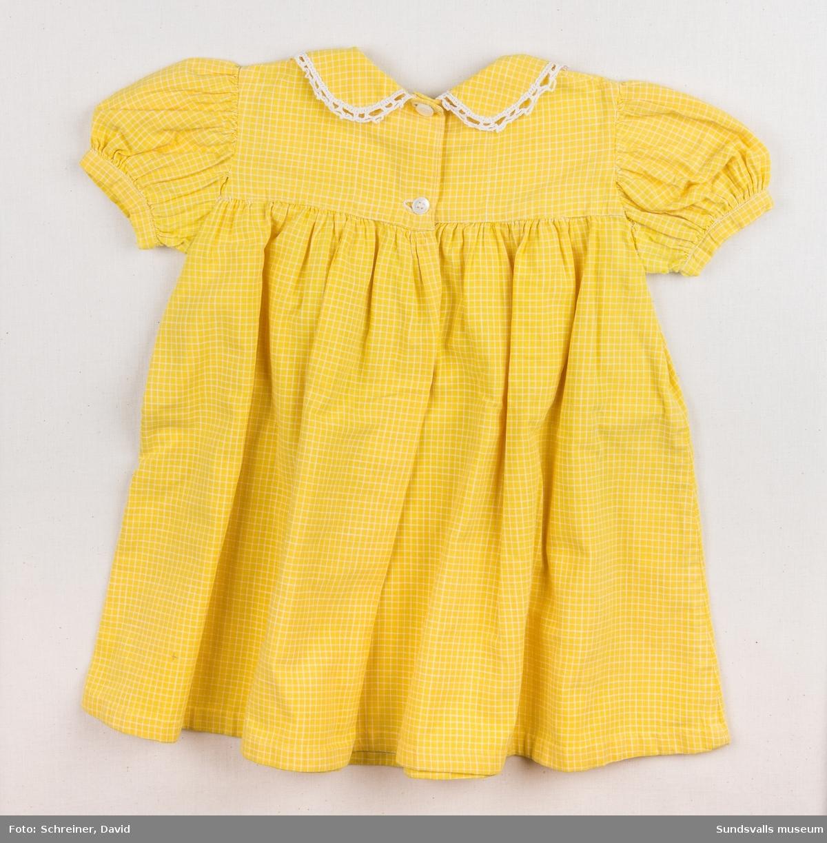 En gul och vit rutig flickklänning med högt skuren midja, puffärmar och en rundkrage med virkad spetskant. Klänningen knäpps med två stycken vita plastknappar i ryggen. Storlek ca 2 år.