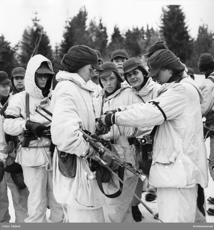 Vinterövning, soldater i tät grupp med vinteruniform och kulsprutepistol m/1945 med lösskjutningspipa.