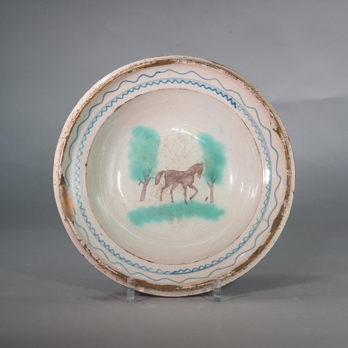 """Fat, lergodsfat, vitglaserat. I mitten schablonmålad och svampad dekor i form av häst i helfigur i mangan samt på var sida träd i grönt och mangan. Runt brättet vågformad blå dekor. S.k. """"Stettiner""""."""