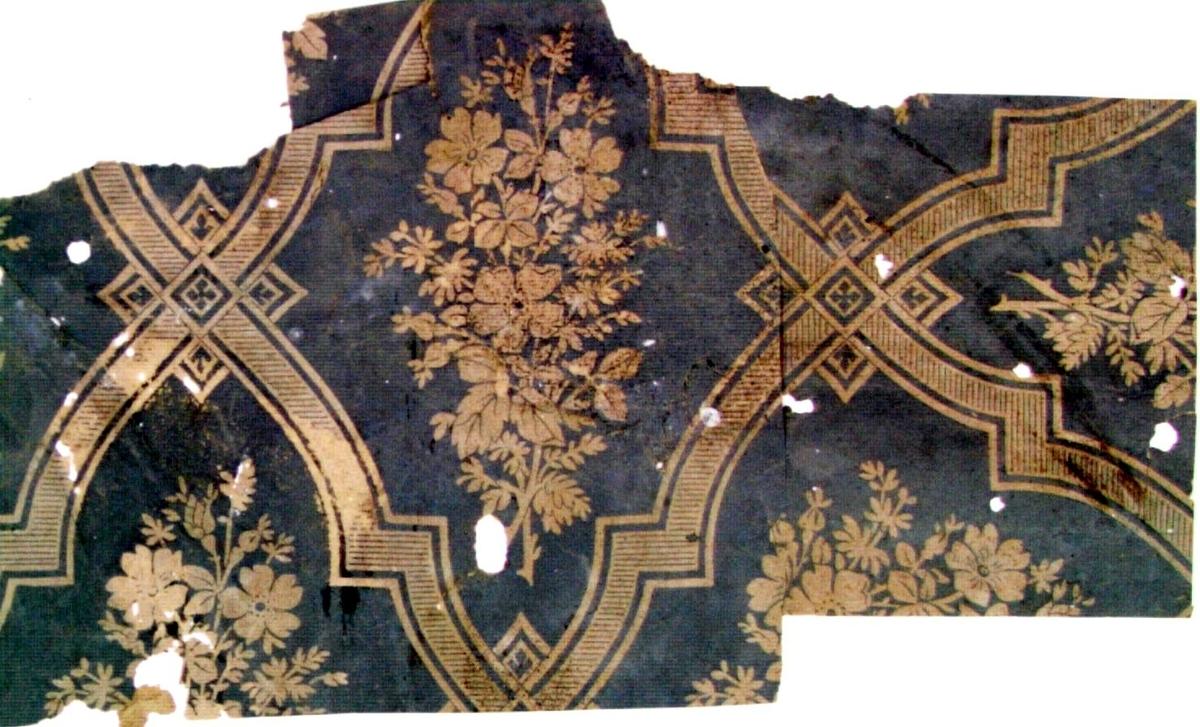 Stort rombmönster dekorerat med en blombukett i varje mönsterdel samt med ett rutornament i varje krysspunkt. Tryck i grått på ofärgat papper.