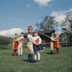 Dansande barn på Orsakullens gräsmatta iklädda folkdräkt.