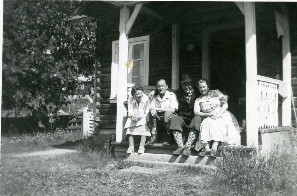 To kvinner og to menn sitter på trappa til gamlestua på Braka, Hedalen, Sør-Aurdal.