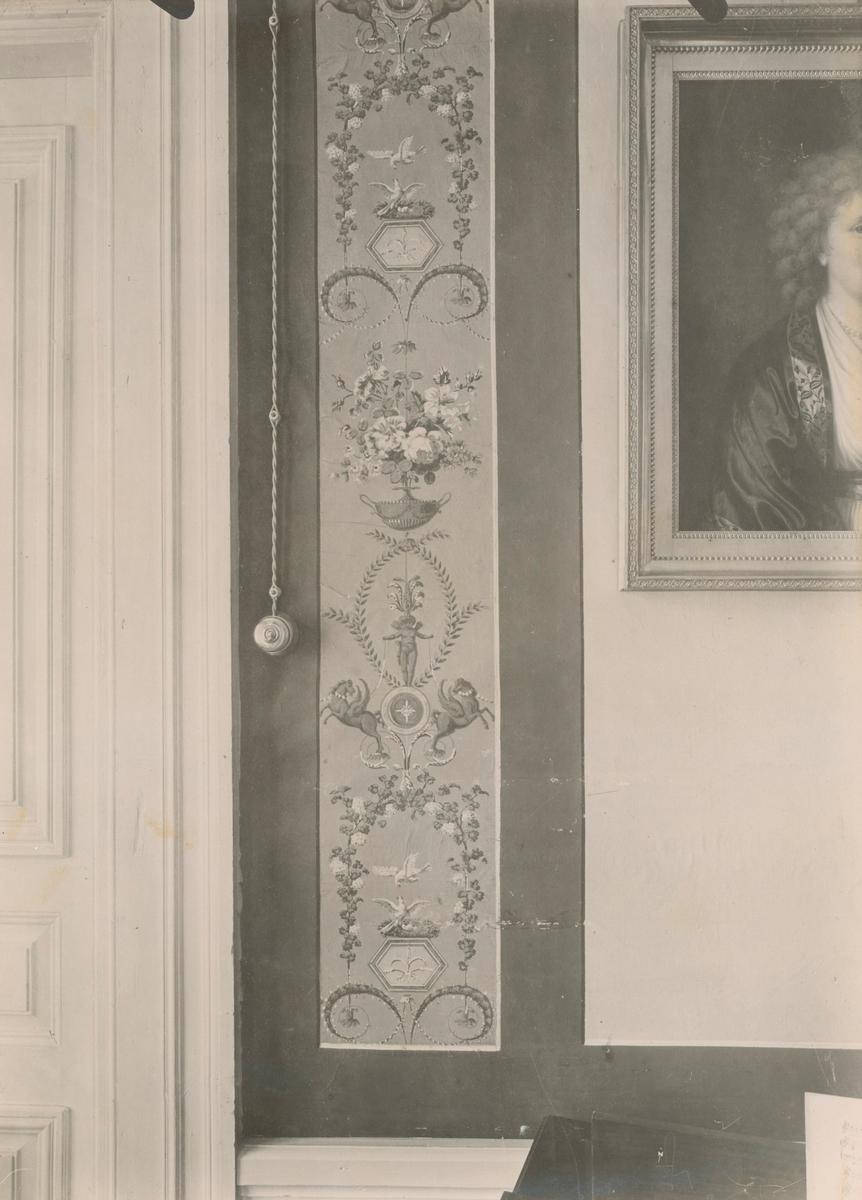 Värnanäs herrgård: det gula förmaket i övervåningen. Pilasterfält av tryckt tapet med mönster i färger mot högblå botten. Svartgrå ramverk och gult väggfält i limfärg.