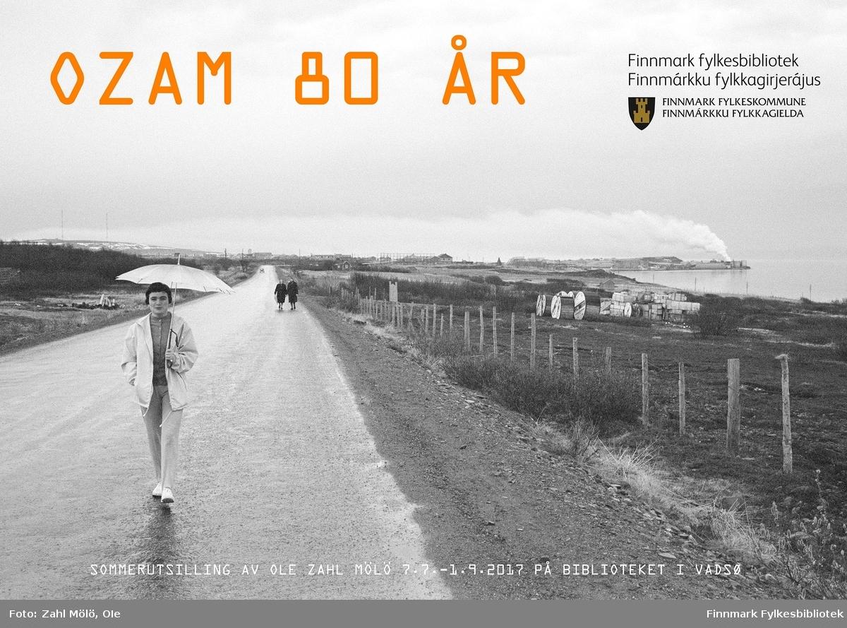 Utstillingsplakat til fotoserie av fotograf Ole Zahl Mölö. Vadsø, 1968. Mennesker på grusvei. Kvinne med paraply i forgrunnen. I bakgrunnen ser man røyk fra skorsteinen til Sildoljefabrikken på Vadsøya.