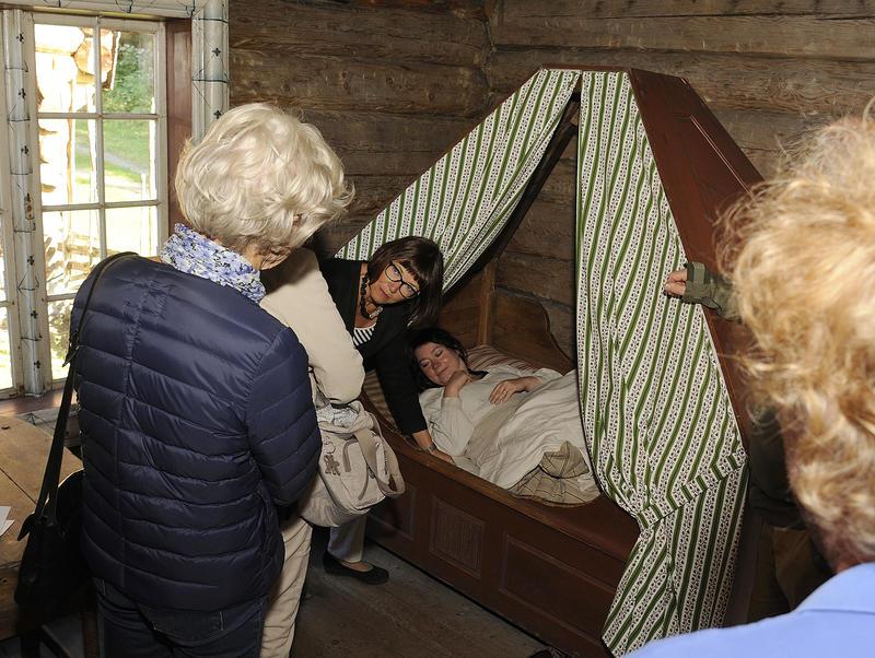 En kvinnelig historiker forteller publikum om ulike sovevaner, i ei slags himmelseng ligger ei kvinne og sover.