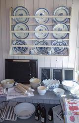 Tallerkenhyle som viser dype og flate tallerkener i hvitt porselen med blå blomsterdekor, kjøkkenhåndklær, boller, kjevler og tavler til å skrive på.