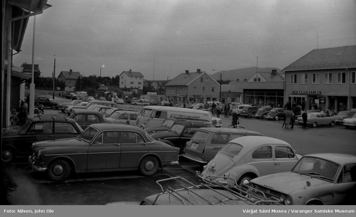 Bossekop i Alta. Alta Samvirkelag til høyre i bildet. Svært mange biler står parkert, muligens i forbindelse med et arrangement.  Alta, Juli 1967