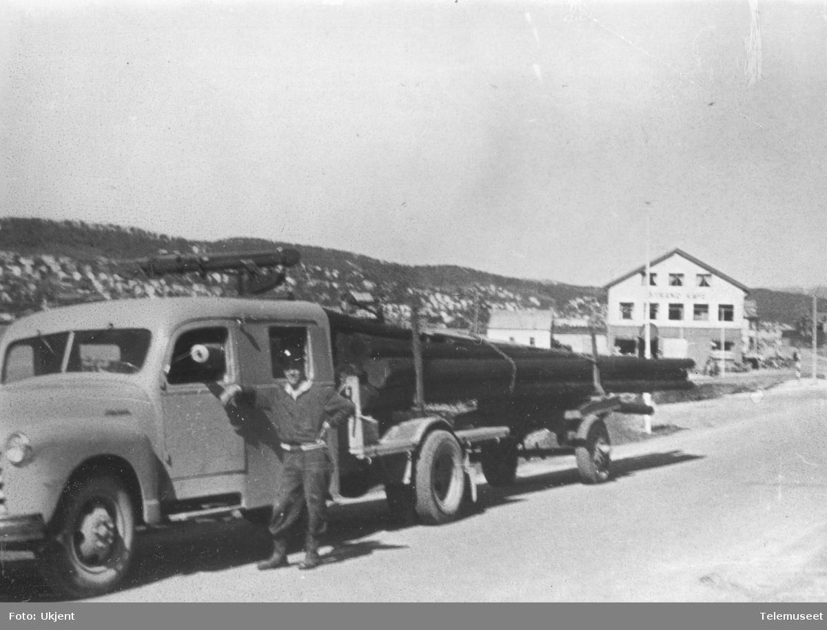 Lastebil med telefonstolper