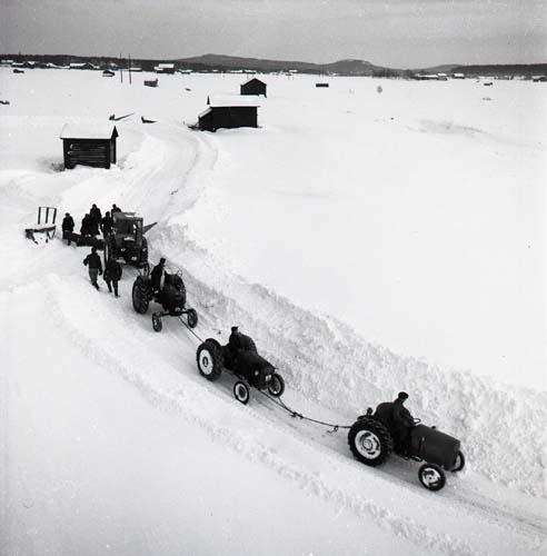 Den 22:a januari 1956 har snön fallit i Glössbo och snövallarna längs vägen har blivit höga. I ett försök att kunna ploga undan den tunga snön från vägen har fyra traktorer kopplats ihop med rep. Förutom männen i traktorerna finns ytterligare sju män på bilden som hjälper till att koppla på plogen bakom sista traktorn i ledet.