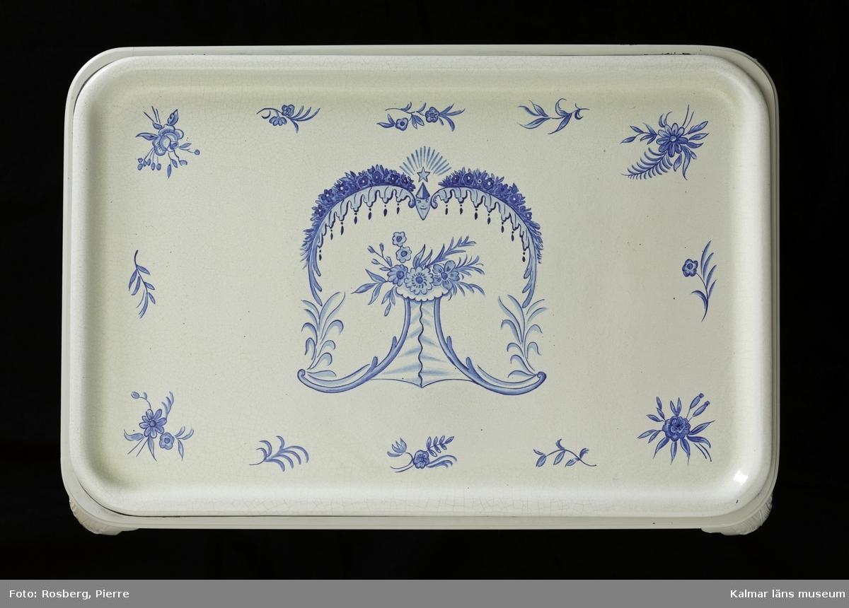 KLM 45127. Bord, brickbord eller tebord, trä och keramik. Bordskiva i form av bricka av keramik, fajans med dekoren i blått mot ljust blågrå bakgrund, på stativ av trä målat ljusgrått, (ej ursprunglig bemålning) har sannolikt varit brunt från början.