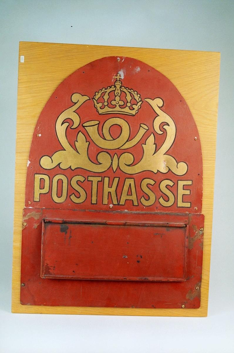 Postinnkast i blikk montert på treplate. Motiv av et posthorn med krone.
