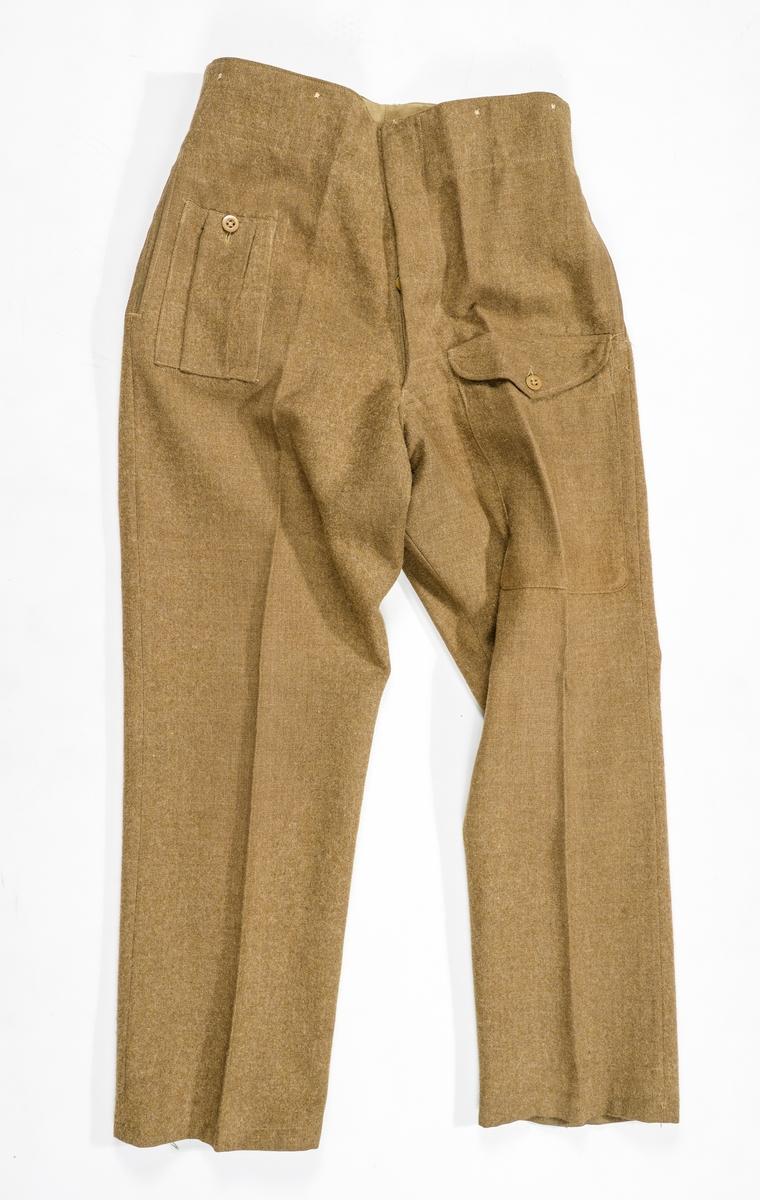 Uniformsbukse i brun-grønt ulltøy. Bukse med rette bein, Fóra på innsida av linninga med brunt bomullstøy. Same tøyet er i lommefóret. Gylf med fem knappar og knappehol. Stikklommer i sidene og ei baklomme. To påsydde utanpålommer på framsida. Høyrer til VFF 09543 Uniformsjakke.