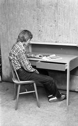 Ung mann som sitter ved pulten og leser et interiørmagasin.