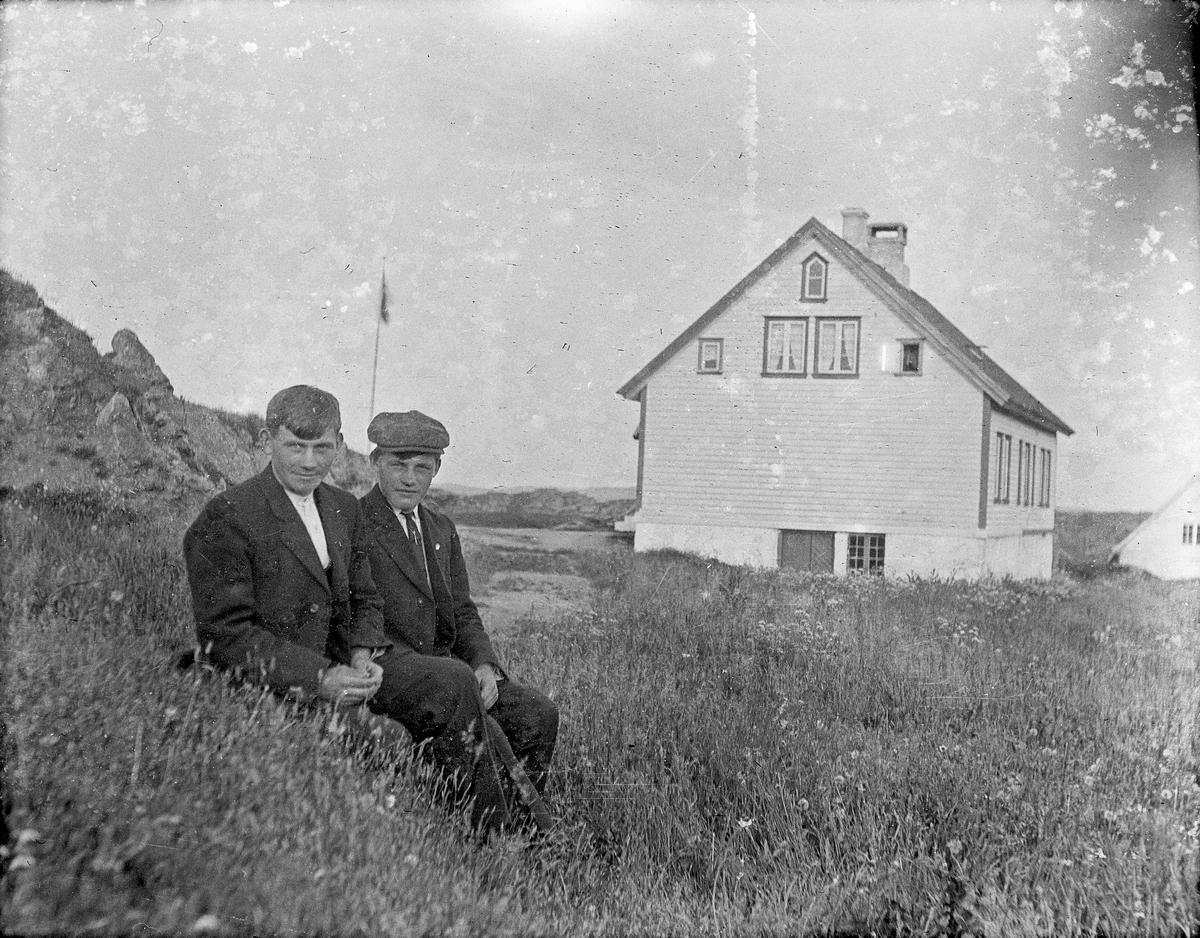 Gruppebilde. 2 unge menn sittende i gresset med bolighus i bakgrunnen. Flagget er oppe.