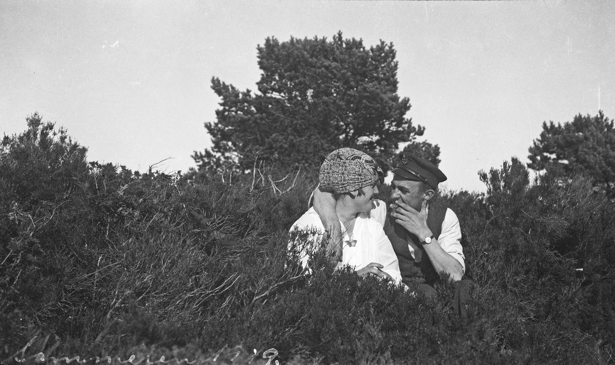Sommer. En kvinne og en mann koser seg sammen i solskinnet. Sitter tett sammen i buskene. Mannen røyker. Hverdagsfoto.