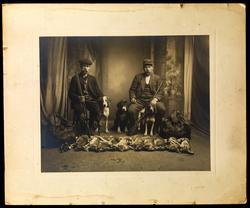 Studiofoto. To menn med våpen, hund og fangst (harer og rype