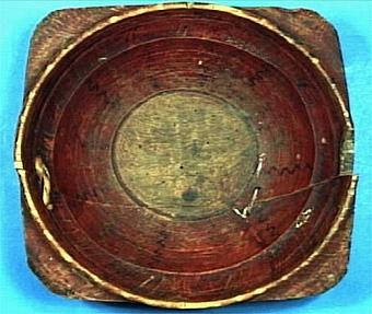 Snibbskål, målad i brunaktigt rött. Skålens insida har målad, geometrisk dekor i form av vertikala streck och vågband i gult och svart. Skålen är sprucken rakt av och lagad med rottråd resp. bomullssnöre i förborrade hål.