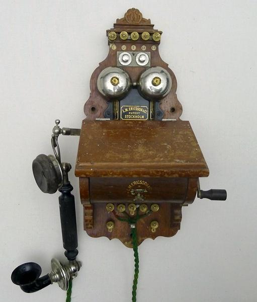 """Enl liggare: """"Telefon, väggtelefon i brunmålat trä med telefonluren hängande på ena sidan och veven på den andra. h 41 cm, br 28 cm, dj 17 cm  Föremålet funnet omärkt i samlingarna 1980  """"LM Eriksson patent Stockholm"""""""