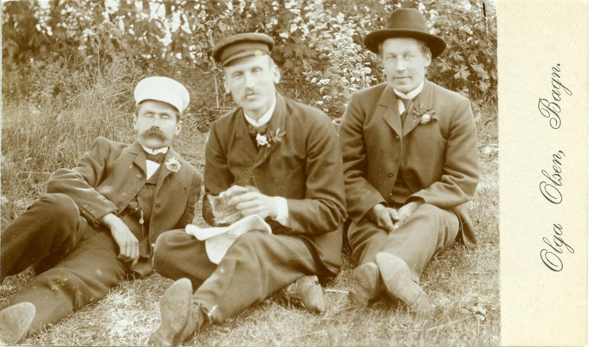 Tre menn sit ute på graset.