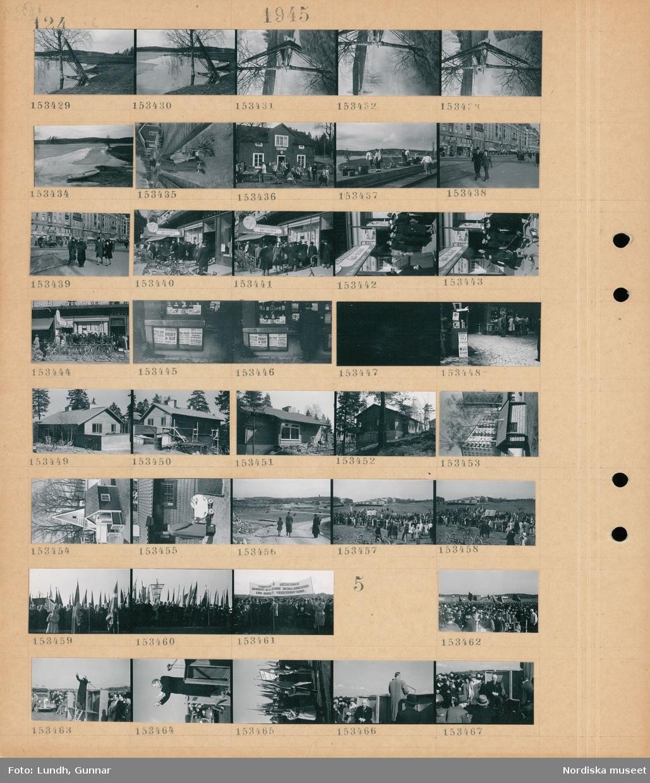 """Motiv: (ingen anteckning) ; Landskapsvy med strand och sjö med is, en kvinna med packning står på en perrong vid en järnvägsstation, människor utanför ett hus med skylt """"Rällså"""", kvinnor och män på en järnvägsperrong, stadsvy med fotgängare, en folksamling vid en tidgningsaffär, löpsedlar """"Tyskland kapitulerar"""" """"Kriget är slut Kapitulation i natt"""" """"Hitler döende"""" """", ett husbygge, en lekstuga, en man med en barnvagn, ett demonstrationståg på Gärdet troligen första maj demonstration, en banderoll """"Studenter för socialismen Solidaritet med de strejkande metallarbetarna Stäng gränserna för krigsförbrytarna"""".  Motiv: (ingen anteckning) ; En folksamling på Gärdet första maj demonstration, en man håller tal, en fanborg, Per Albin Hansson sitter bakom ett podium."""
