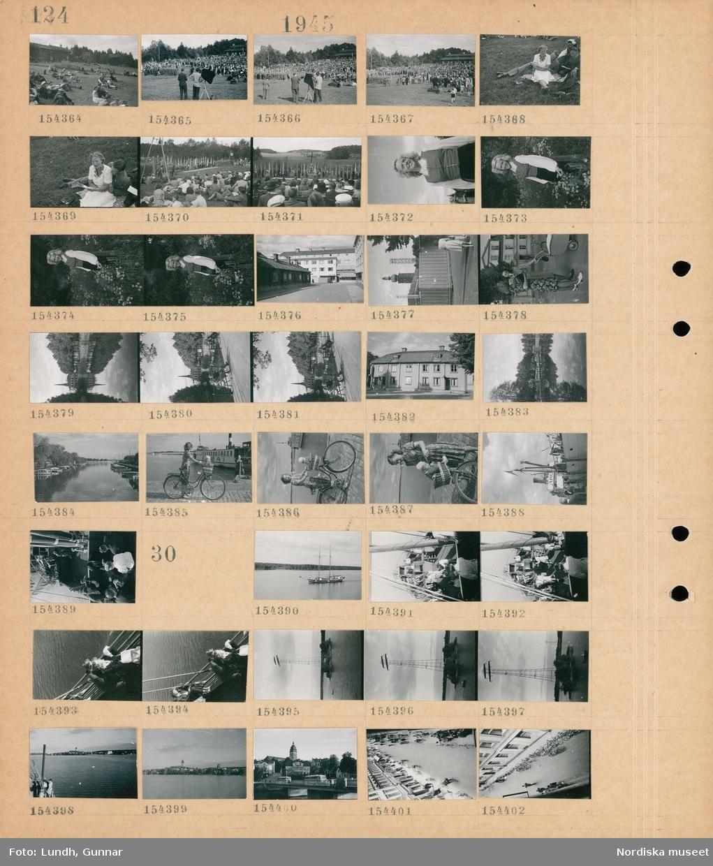 """Motiv: (ingen anteckning) ; Människor sitter på marken, en folksamling, en fanborg och en midsommarstång i bakgrunden, porträtt av en kvinna, exteriör av en byggnad, två kvinnor med en barnvagn, människor sitter på parksoffor vid en kanal, exteriör av hus, vy av hamn med båtar, en kvinna med cykel med ett barn i en korg på styret, människor vid ett förtöjt fartyg """"Aros"""", människor på däcket på ett fartyg.  Motiv: (ingen anteckning) ; Ett fartyg på vattnet, människor på däcket på ett fartyg, landskapsvy med vatten och bebyggelse, stadsvy med bussar och bro, stadsvy med fotgängare - cyklister och parkerade cyklar."""