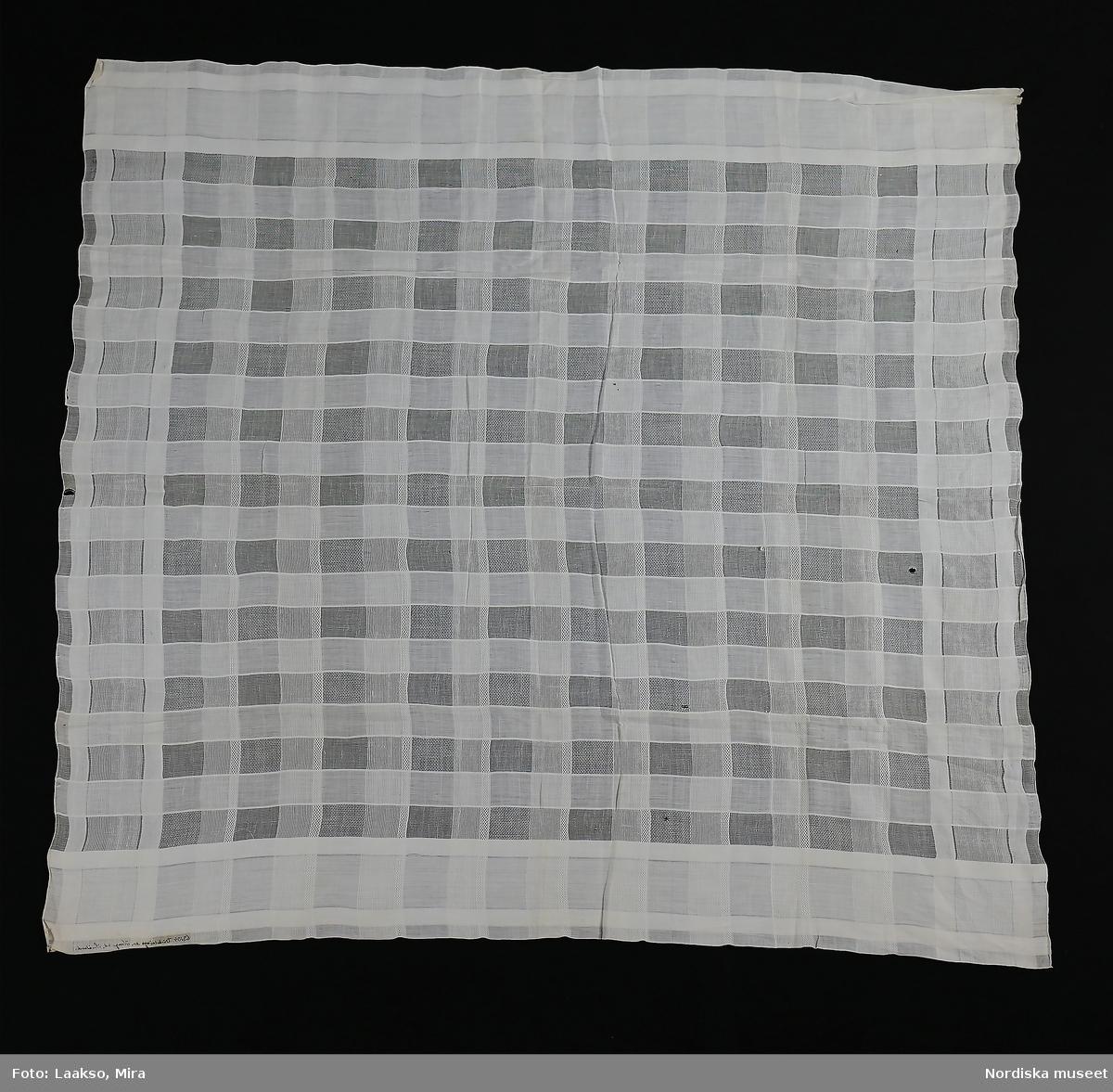"""Stort kläde, använt som huvudduk, av tunn fabriksvävd bomullsvävnad, rutig i tätare och glesare väv med olika bottnar i de glesa rutorna. 2 stadkanter och 2 ytterligt tunna handsydda fållar. Bilaga: """"Nytjad som huvudduk i Väckelsång socken."""" /Berit Eldvik 2010-06-23"""