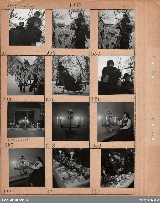 Motiv: Stockholm, släde med två förspända hästar på snöig väg, slädnät, kusk och tre passagerare, stadshuset, dukat bord med julprydnader, tända ljus, julgran, ljusstake med fot i form av hästar, kvinna klädd i folkdräkt tänder ljus, dukat kaffebord med tända grenljus, lussekatter, pepparkaksfigurer, halmprydnad, kvinna i ålderdomlig klädsel vid kaffebord.