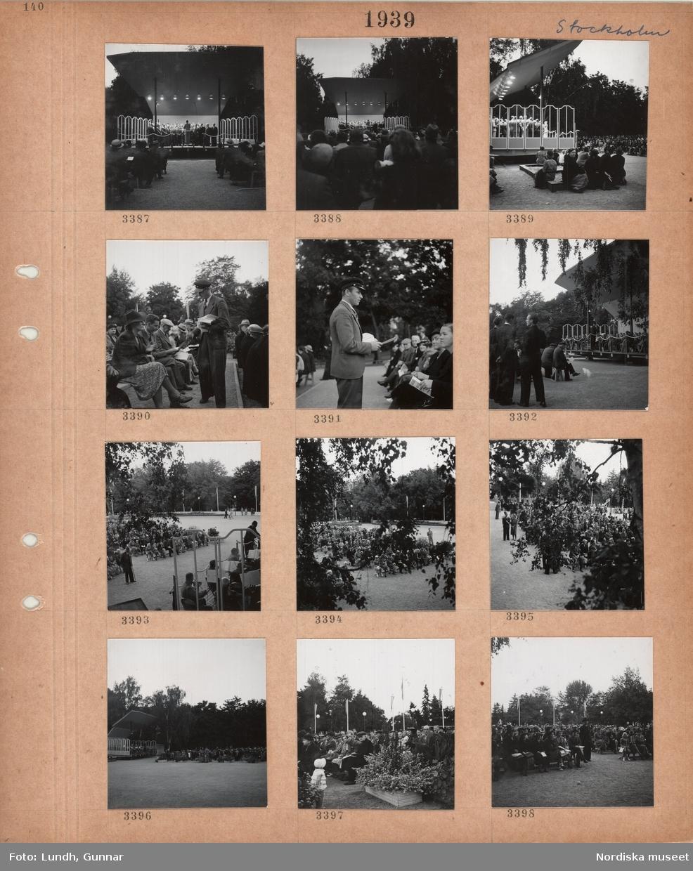 Motiv: Stockholm, utomhusscen i en park, kör med dirigent, sittande publik, man i skärmmössa delar ut programblad, orkester.