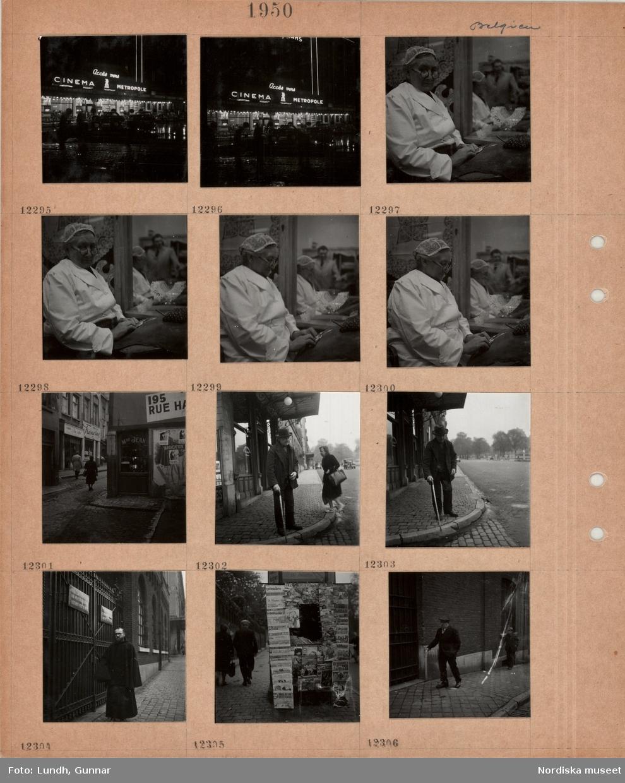 Motiv: Belgien, stadsgata i regn på kvällen, neonskyltar, biograf, en äldre kvinna i spetsmössa arbetar vid knyppeldyna, stenlagd gata med butiksfönster och skyltar, gående, en äldre man med käpp står vid trottoarkant, kvinna med shoppingväska, en man i munkkåpa står vid en smidesgrind, tidningsstånd på trottoar, man med käpp går på trottoar.